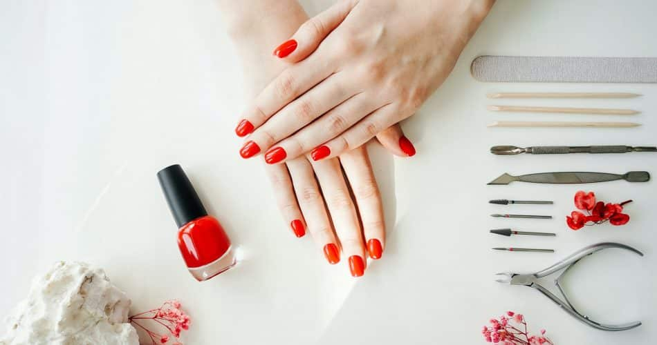 Manicured woman's nails with red nail polish.